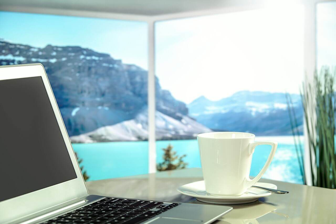 Travel Tips for Tech Savvy Entrepreneurs - Laptop, Coffee Cup, & a Beautiful View