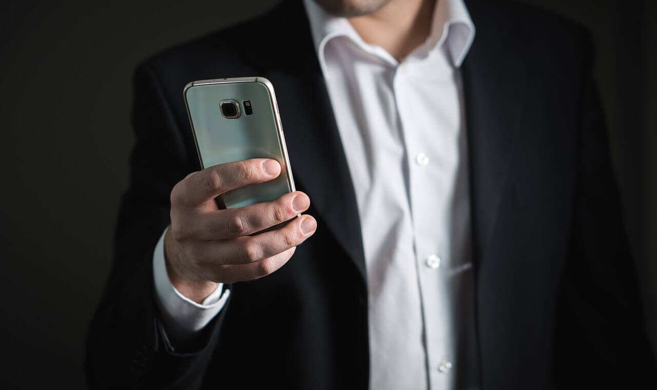 Why Your Business Needs to Archive Text Messages - Business Man with Phone Texting