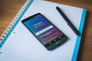 How Can You Use Instagram for Promoting Your Startup Business - phone on notepad